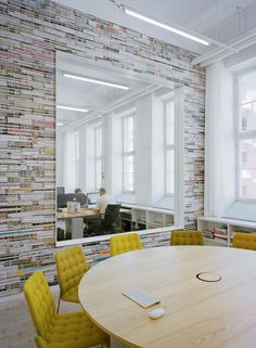 an awesome meeting room with a magazine wall and giant window into the workspace. Oh and fabulous yellow chairs!