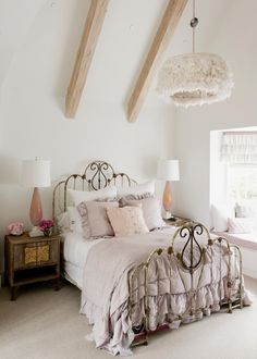 Ruffled bedding in a muted lavender hue adorns the ornate wrought iron bed in this enchanting girl's bedroom. A frilled light fixture complements the bedding, and crisp white walls lend a bright, fresh feeling to the room.