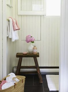 source: Anne Hepfer Designs Sweet cottage bathroom with white plank walls paired with slate tile bathroom floor. Rustic sawhorse stool, hidden bathroom cabinet and white and pink bath towels.