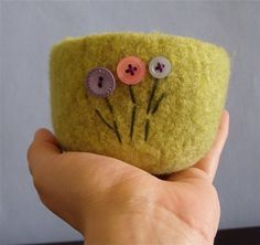 This sweet little bowl is made from a moss green 100% wool yarn and has three buttons as flowers. The buttons are lavender purple, pink, and pale sky blue. I used 100% cotton embroidery floss for the stems and leaves in dark green.    This soft little felted bowl would look great at the office with paperclips or rubber bands in it, or you can use it at home to consolidate some small things like hair elastics, loose change, earrings, etc... Many of the people who purchase these bowls from me…