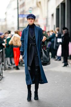 A model wears a beret hat a blue coat outside Alexis Mabille during Paris Fashion Week Haute Couture Spring/Summer 2018 on January 23 2018 in Paris...