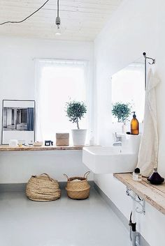 Polished concrete with white painted walls, industrial style sink. Wooden shelving and wicker bassets to soften.