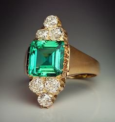 An Antique Colombian Emerald and Old Mine Cut Diamond Ring, Circa 1890. A 14K yellow gold ring of a modified marquise shape centered with a sparkling eye clean 2.50 carat square-shaped step cut Colombian emerald, flanked by six old cushion cut diamonds.