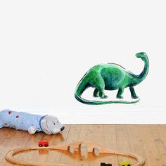 Reusable, removable, and repositionable decal! Created from an original watercolor illustration and made from a woven fabric with a self-adhesive backing. Henry the Dinosaur has been painted using layers of translucent and fluid watercolours to build up rich colours and textures. Dinosau