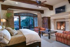 Traditional Master Bedroom with Hand Forged Fireplace Doors, stone fireplace, Lavish Home Bed Quilt, Exposed beam, Carpet
