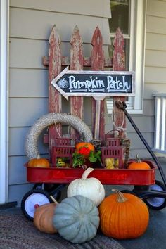 Cute Country Fall Porch Decor! An Old Picket Fence, Pumpkin Patch Chalkboard Sign, and Vintage Red Wagon filled with Lanterns and surrounded by Pumpkins.