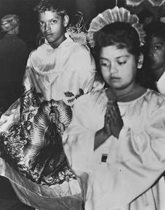 "[AHS 62761]  Feast Day Pageant of the Virgin de Guadalupe, 1955.  Local children celebrate the Virgin de Guadalupe in this procession that recreates the appearance of the Virgin de Guadalupe—patron saint of the Americas— to Juan Diego near Mexico City in the sixteenth century. The boy playing Juan Diego wears an apron-like tunic or ""tilma"" with the image of the Virgin on it symbolizing the imprint that was said to have miraculously appeared on Juan's garment when he collected roses at…"