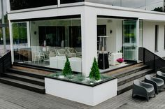 The retractable glass walls complement the minimalist design of this contemporary home. Outside House Paint Colors, Paint Colors For Home, Glass Roof, House Painting, Sunroom, Minimalist Design, Terrace, Entrance, Pergola