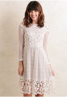 This cream-toned, fit-and-flare dress features an all over, delicate floral lace design with contrasting bold lace details along the bust, hem, and yoke. Finished with a nude-toned lining and hid...