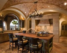 Multiple colors of stone and brick in this kitchen keep the tone warm and inviting.