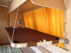 Original airstream stowable bunk beds. Bracket on wall; hang cord from ceiling.