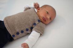Sød, lille, asymmetrisk cardigan til de nyfødte. Den strikkes ovenfra og ned og er uden sømme. Her er brugt ret tyndt uldgarn, men den kan strikkes i mange garntyper.