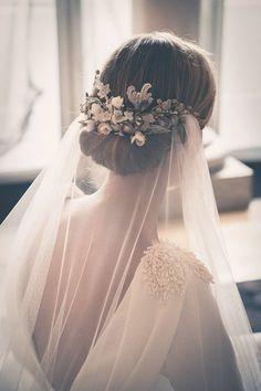 Coque baixo com véu transparente e grinalda grega de flores.