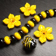 Lampwork glass bee and flower beads by Laura Sparling