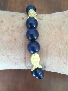 IV Bracelet en perles de bois et poissons plaqués or