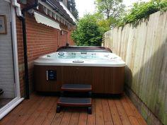 Jacuzzi® J-385™ posé sur une terrasse en bois.