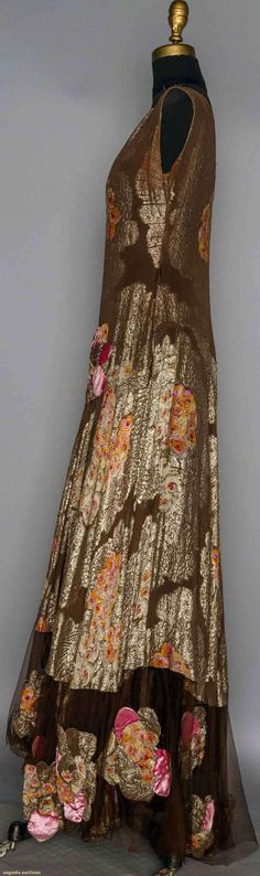 1930 Chocolate brown silk brocaded in gold lame cartouches w/ printed orange & pink blossoms, net hem edge w/ printed lame appliques. Sideway