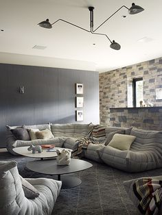 This Lake Tahoe playroom is outfitted with Ligne Roset Togo sofas by Michel Ducaroy, Phoenix coffee tables by Patricia Urquiola and a custom Moroccan rug by Jamie Bush + Co. The ceiling light is by Serge Mouille from Guéridon. Photo by Ngoc Minh Ngo