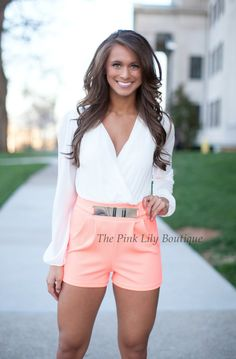 This head-turning romper features a plunging V-neck, long sleeve top, and neon coral, faux belted, sexy, short bottom! Pairs perfectly with wedges!