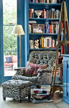 An étagère found by the client in a Magazine Street antique shop sits next to a mod zebra upholstered chair with vintage pillow- Melissa Rufty of MMR Interiors