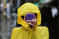 A Filipino resident takes pictures using her smartphone outside a flooded village as Typhoon Rammasun batters suburban Quezon city, north of Manila, Philippines, on July 16. Typhoon Rammasun knocked out power in many areas but it spared the Philippine capital, Manila, and densely-populated northern provinces from being directly battered Wednesday when its fierce wind shifted slightly away, officials said. (Aaron Favila/Associated Press)