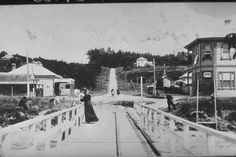 Looking from St Heliers Bay wharf (foreground) up St Heliers Bay Road (centre) with St Heliers Bay hotel (right) and a woman in the costume of the time standing on the wharf Flatmates Wanted, The St, Auckland, Historical Photos, New Zealand, Saints, Fair Grounds, Street View, Black And White