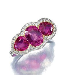 RUBY AND DIAMOND RING. Set at the centre with a cushion-shaped ruby weighing 1.37 carats flanked by two pear-shaped rubies weighing 1.08 and 0.73 carats respectively, within borders and between shoulders millegrain-set with brilliant-cut diamonds