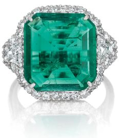 An Important Emerald and Diamond Ring.    Set with a square-cut emerald, weighing approximately 5.56 carats, flanked on either side by a trapeze-cut diamond, within a pavé-set diamond surround and gallery, mounted in 18K white gold, size 6.With report no.CS47207 dated 13 December 2012 from the American Gemological Laboratories, stating that the emerald is of Colombian origin, with insignificant clarity enhancement. Via Philips.