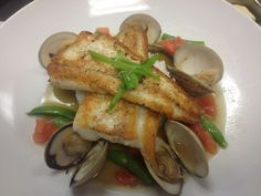 Seared flounder with clams in a seafood broth with sugar snap peas, tomato confit with jasmine rice.