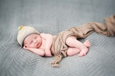 Adorable sleeping newborn baby boy with hat on light blue baby blanket. Photographed at Julie Saad Photography in Williamsburg, Brooklyn.