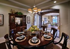 ( No. 3) Love the interior decor of this Toll Brothers home: dark wood furniture, stone work on arches (so cool), crown molding, neutral colored walls. Those powder blue napkins really pop! Contemporary interior design style