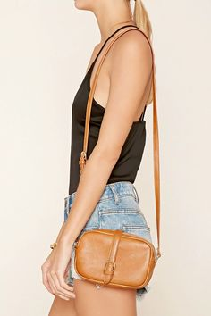 A faux leather crossbody bag featuring a snap-button front with a buckle, an exposed zipper, high-polish accents, one interior pocket, an adjustable shoulder strap, and a structured design.