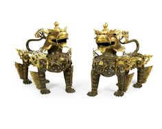 A pair of late 19th/early 20th century patinated and painted bronze models of standing East Asian Buddhistic lions (2)