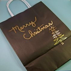 Hand decorated gift bag, with greeting and Christmas tree.