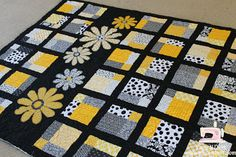 I've mentioned before that I live in a fairly small town. A town with just one high-school. The high-school colors are black and gold. Since gold isn't an easy fabric color to come by lots of quilts here are made in black and yellow.  Genny made this Wasatch quilt. It's so cute isn't it!I machine quilted it for her.