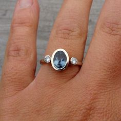 A lovely 8mm x 6mm fair trade blue sapphire sits in a heavy, tapered 14k white gold bezel, flanked by two 3mm bezel-set moissanites, on a comfort-fit, 2mm wide 14k white gold band. All of the metal used in this ring's construction is from recycled sources.