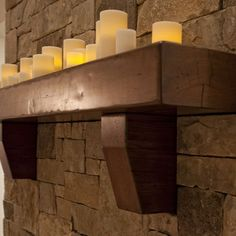 wood fireplace mantle with tons of candles.