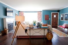 love love love the wall color, the tripod lamp, the bell jar of letters, the iron legged table