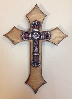 """Miniature wooden, double layer, wall cross. The back cross is stained with danish oil and then slightly distressed with black acrylic paint. The piece is topped with a faux leather belt cross with ornate silver accents, horseshoe and Texas Star. Dimensions are approximately 5"""" x 7"""". Each cross is handmade with love and truly one of a kind."""