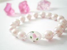 Beautiful beaded stretch bracelet with pale pink glass rose bead. Simple and great for everyday life and special occasions!  Unique and softly romantic gift idea for any special women in your life.  -Pale pink stardust beads (8mm) -Clear color seed beads -Oval shaped glass bead that has beautiful rose pattern - Very strong elastic cord  If you would like shorter or longer lengths for your bracelet just put a note in at checkout. Please remember when measuring your wrist to add 0.5 inches, if…