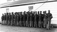 HOW DISEASE DECIMATED BLACK SOLDIERS IN THE CIVIL WAR Black and white civil war soldiers with weapons in a line looking at camera