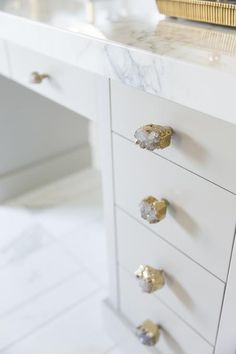 Beautiful bathroom features a gray make up vanity adorned with Anthropologie Crowned Quartz Knobs ...