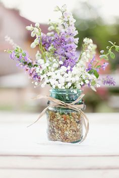 sprigs of lavender, purple lantana, rosemary, lockspur, delphiniums, and baby's breath in blue transparent mason jars with raffia bows tied around the lip