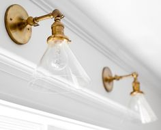 Brass and glass sconces. The brass and clear glass sconces are The sconces are Princeton Sophomore Sconce in Natural Brass from Schoolhouse Electric. Wall Lights, Sconces, Bathroom Lighting, Renovation Design, Visual Comfort Lighting, Sconce Lighting, Brass Lighting, Kitchen Renovation Design, Visual Comfort