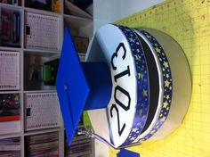 Wooden cheese wheel box covered in wrapping paper and a graduation hat made of poster board