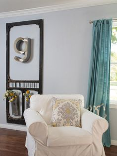 """As seen on HGTV's Fixer Upper, host Joanna Gaines created a personalized piece of art for this living room using a metal letter """"g"""" framed with an old screen door. A slipcovered white chair and country blue window treatments enhance the room's French Country style."""