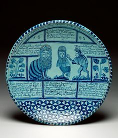 English Delftware charger with a cat, an owl and a monkey dark buff earthenware, moulded, the front tin-glazed duck-egg blue and painted; the reverse covered with lead-glaze; the footring is pierced by a hole. Height 8.3cm, diameter 39cm, dated 1688.