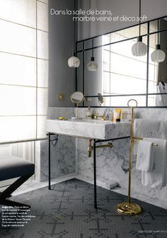 gold fixtures in bathroom contrast the black & white of marble, pendant lights, via Elle Decor France
