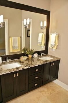 Granite tops and framed mirror with wall sconce lighting