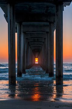 """perfect timing, sunrise sunset as viewed down the """"tunnel"""" under a dock with the sun aligned perfectly at the center of the dock posts"""